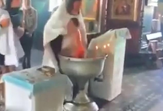 أم تنقضّ على قس روسي وهو يغرق طفلها بعنف في الماء أثناء تعميده! فيديو صورة رقم 3