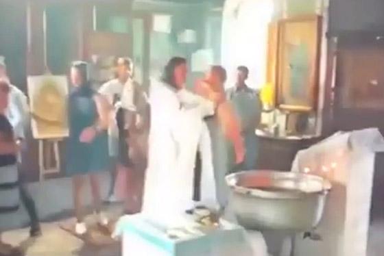 أم تنقضّ على قس روسي وهو يغرق طفلها بعنف في الماء أثناء تعميده! فيديو صورة رقم 2