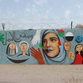 صور: شباب عراقيون يرسمون على حوائط شوارع بغداد لاعادة  البهجة والبسمة  ..