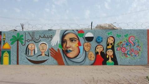 صور: شباب عراقيون يرسمون على حوائط شوارع بغداد لاعادة  البهجة والبسمة للعاصمة واهلها